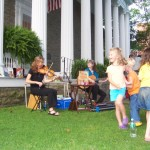 children dancing on the lawn while string instruments play in the background