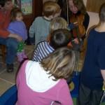 children examining a fiddle
