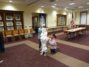 children wrapping another child with toilet paper