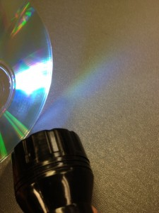 flashlight shining on a CD to create a rainbow