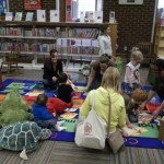 children and caregivers sitting on a rug with books