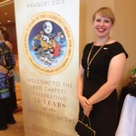 woman posing with banquet banner