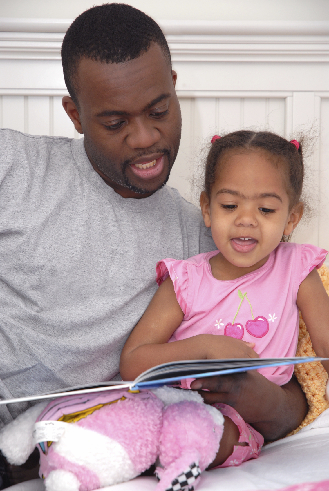 A father reading to his daughter