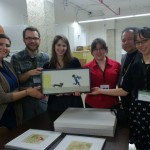 The ambassadors pose with a framed piece by Ezra Jack Keats in the closed stacks of the de Grummond Collection.
