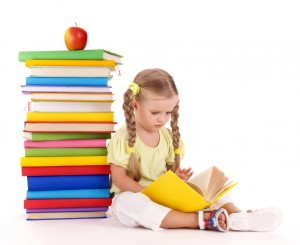 Girl reading by a stack of books