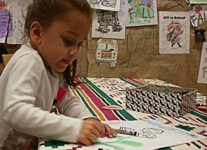 A child colors at a Día program at Skokie Public Library (image courtesy of ALSC).