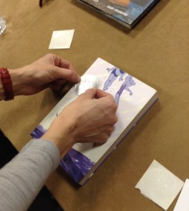Committee member Tali Balas add sticker to the book. Photo by Angela Reynolds
