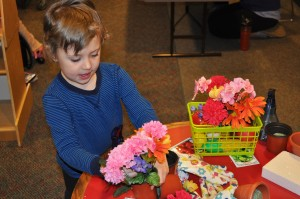 child placing flowers into a pot