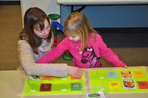 child and adult playing with a Velcro board