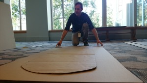Warren uses a template to measure and cut a cardboard sheet. Photo credit: Amy Seto Forrester