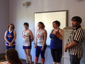 Four derby skaters and a referee from Burning River Roller Derby visiting book club! Photo by Nicole Martin.