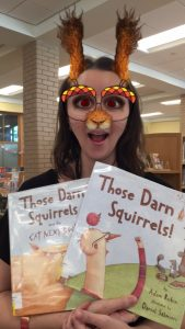 librarian holding Those Darn Squirrels books