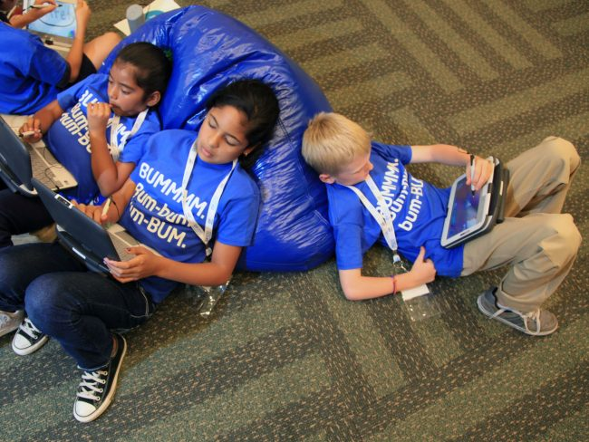 Three children laying on bean bags looking at their tablets.