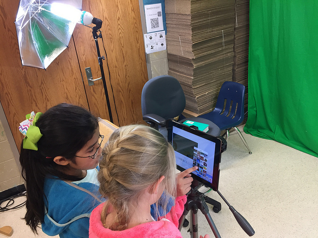 Two students using video editing softwareon tablet while filming in front of a green screen.