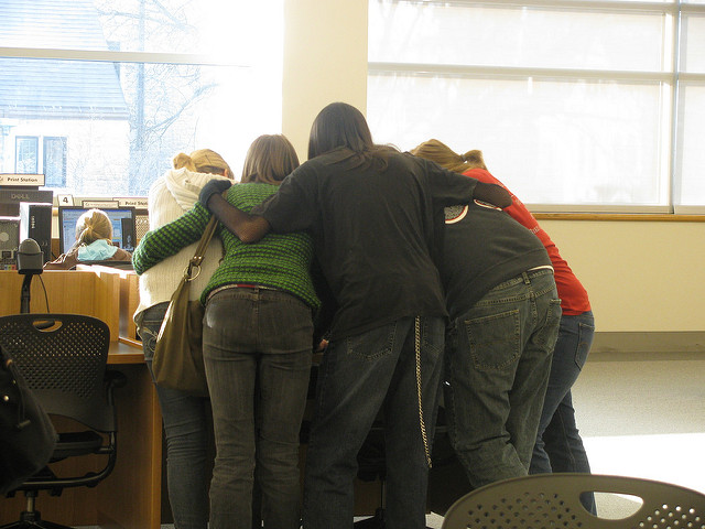 Teens huddled around computer