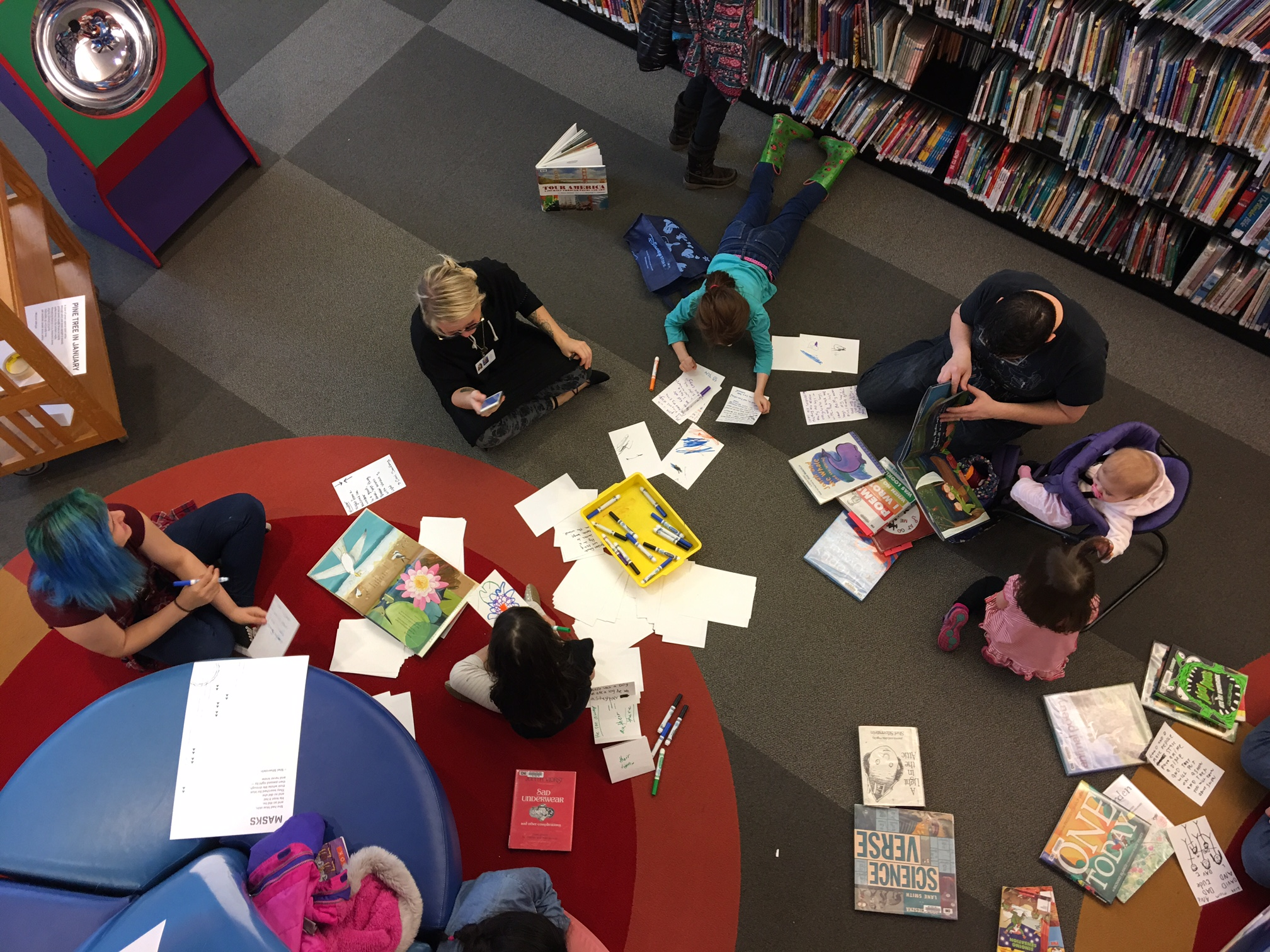 A picture taken from above of kids enjoying a poetry program