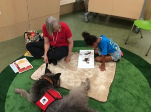 Photo of a child reading with a dog and adult
