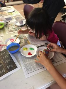 Children paint rocks on a table covered with newspaper