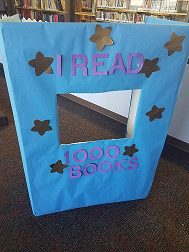 Cardboard photo op or standee with blue paper, gold stars and the workds I Read 1000 Books