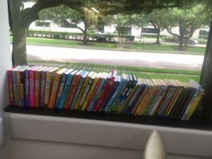 A row of books sitting on a windowsill of a room where a doctor talks with parents