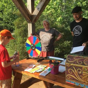 people at table with prize wheel