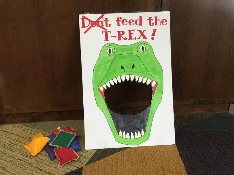 "Picture of ""Don't Feed the T-Rex"" bean bag toss. An image of a green dinosaur with a hole where his mouth would be, with bean bags sitting to the side"