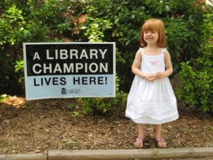 Little girl next to Library Champion sign