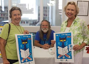 Library patrons holding Pete the Cat posters and library card, with James Dean in background