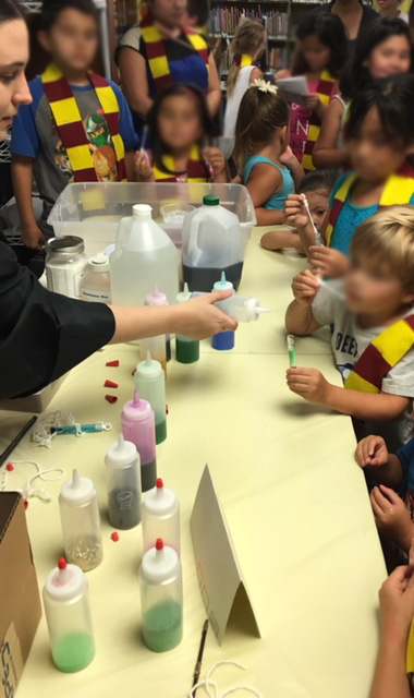 Children line up at a table to check out Harry Potter potions