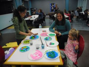 a happy parent and children at the an art workshop at the Athens Clarke County Library