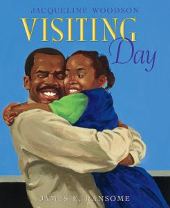 Cover of Visiting Day by Jacqueline Woodson, Illustrated by James E. Ransome, shows a girl hugging her father.