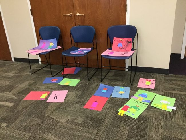 Kindergarten Bootcamp: around twenty pieces of paper laying on the floor and chairs; children's artwork (self-portraits) are on each piece.