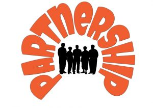 "Image of a group of people with the word ""partnerhsip"" formed around them."