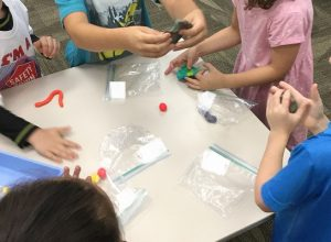 Four Kindergarten Bootcamp students work on mixing primary colored balls of playdough to create the secondary colors. Plastic bags on the table hold the balls of playdough.