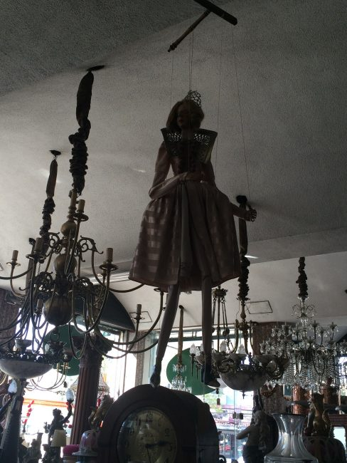 A marionette hanging in the shadows among other puppetry items