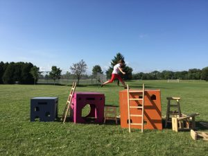 A girl jumps from one play structure to another.
