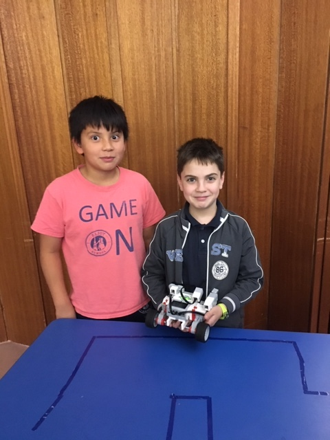 A boy in a salmon colored shirt stands next to a shorter boy in a blue jacket and shirt. The boy in blue rests an EV3 robot on a blue table. Both boys are smiling.