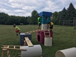 Young children build a structure in a field.