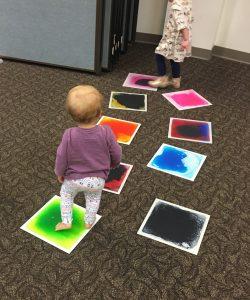 A toddler walks on liquid tiles as part of a Sensory Play program