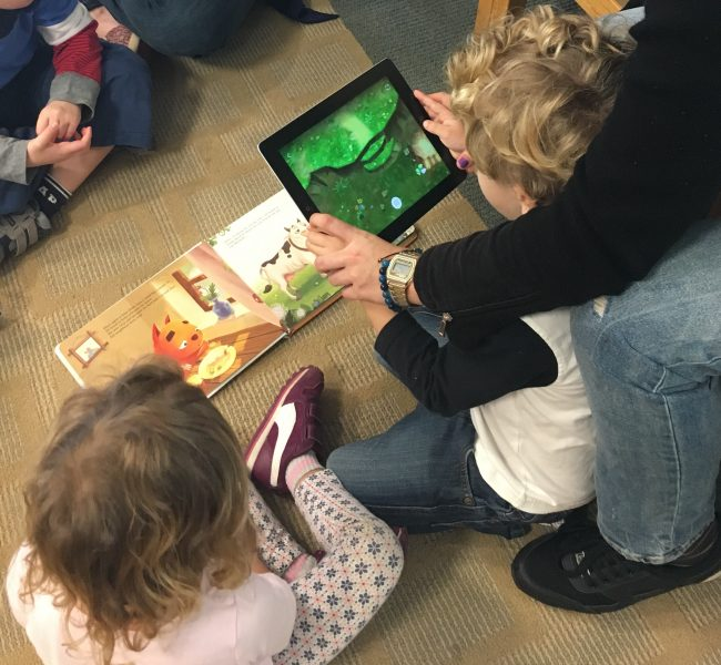 children looking at book and tablet