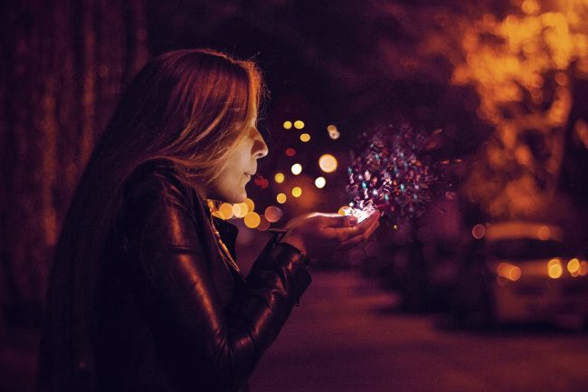Woman blowing sparkles from her hands