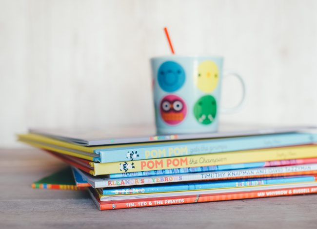 A cup on top of a stack of picture books