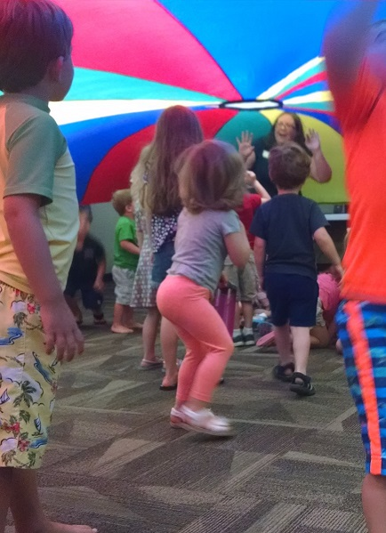 Several children stand underneath a giant parachute. Most of them are blurry from action. In the middle stands a librarian, holding up part of the parachute.