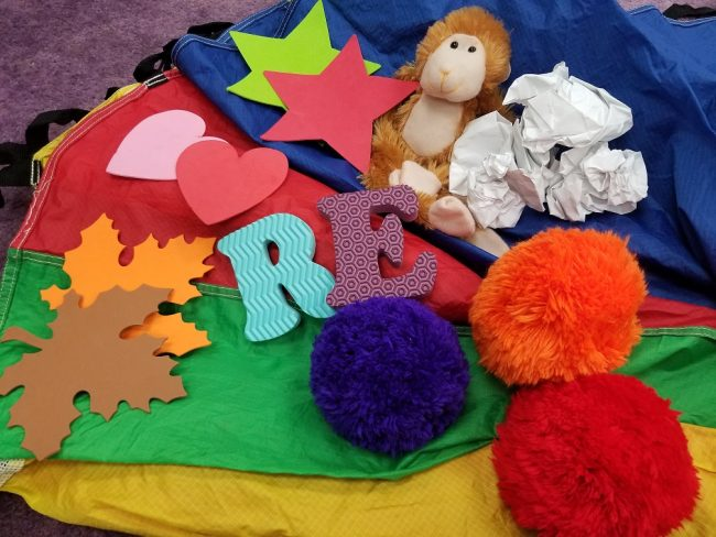 On top of a red, yellow, green, and blue parachute are shown the following toys: foam leaves, foam hearts, foam stars, a stuffed monkey, crumpled up white paper, three fabric balls, and two foam letters.