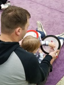A grown-up male and child sit together with two drums and two mallets on a purple rug.