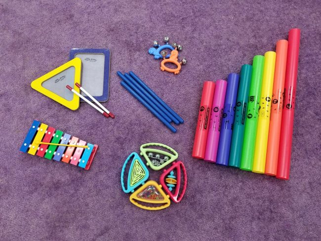 Instruments in storytime are pictured on a purple rug. They include two small hand drums, rhythm sticks, bells, Boomwhackers, hand shakers, and a xylophone.