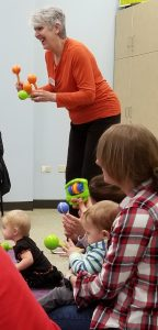 A woman in an orange shirt is shaking two maracas in front of an audience of babies and caregivers.