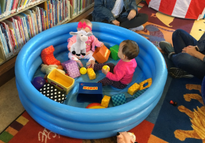 Two babies in a blow up baby pool filled with soft baby toys.
