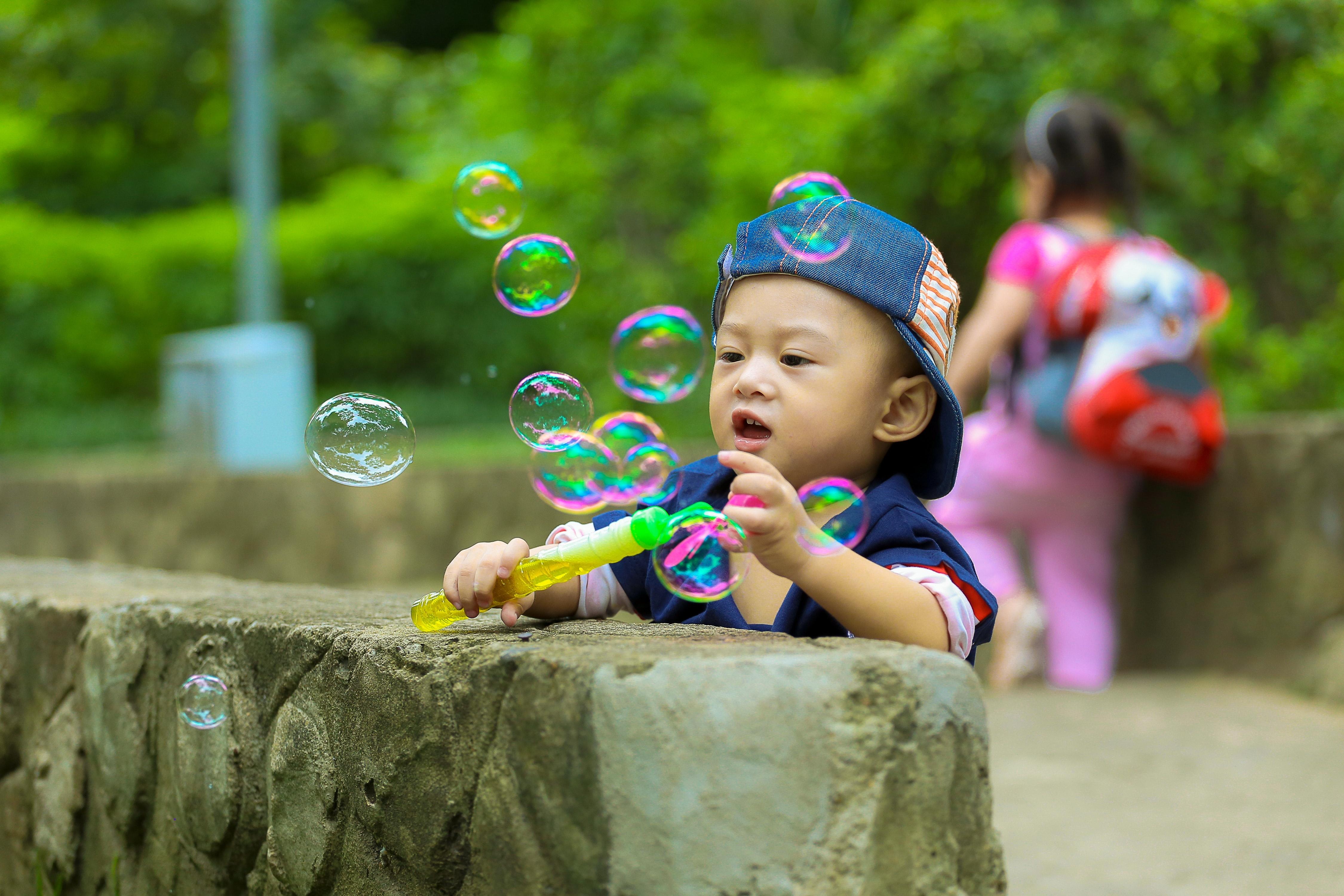 Little boy blowing bubbles.