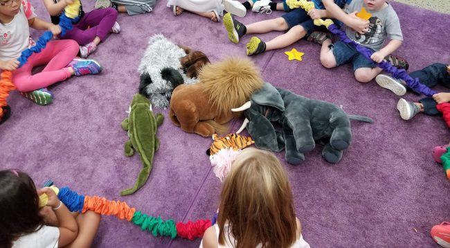 Children sit on a purple rug, holding the multi-colored fabric rubber band (the stretchy band), with a pile of puppets in the middle of the circle.